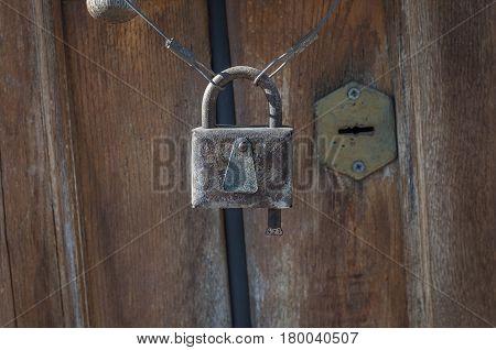 Old rusty closed lock against the brown door