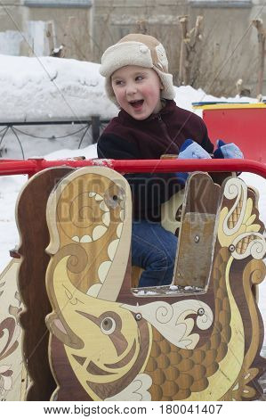 The Happy Little Boy Rides A Roundabout In The Winter.