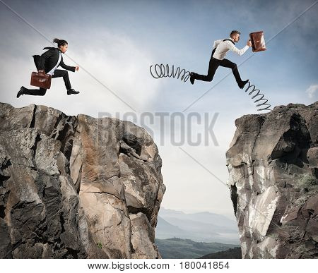 Businessman with spring runs against another businessman between two mountains