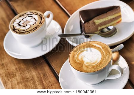 Two Cups Of Cappuccino Coffee And Chocolate Mousse Cake