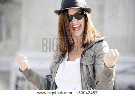 Young and funny hipster woman in a hat is joking with hand signs of success. Lifestyle concept.