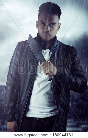 Man wearing a black leather jacket holding a knife in the rain. Book cover design