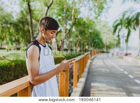 Attractive young sportsman playing and listening to music from smartphone at public park.