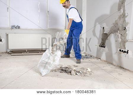 Manual worker shoveling rough rubble into debris bag at construction site.