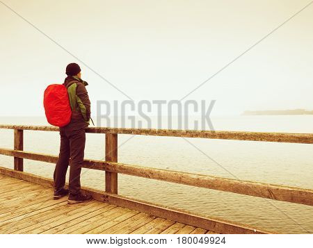 Tourist With Red Backpack On Wooden Sea Pier. Man In Trekking Suit