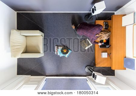 Top view of a man changing the vinyl on the turntable
