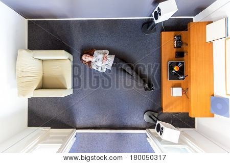 Top view of a woman chilling out on the floor on her back listening to music