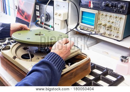 A hifi repairer putting a disc part in a turntable