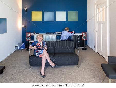Woman reading a magazine while her husband in the background puts on a vinyl record