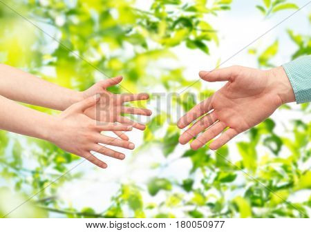 family, childhood, fatherhood, help and people concept - father and child hands over green natural background