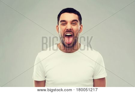 expression, rudeness and people concept - man showing his tongue over gray background