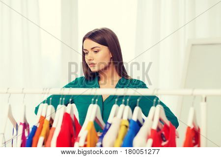 nothing to wear, clothing, fashion and style concept - woman choosing clothes at home wardrobe
