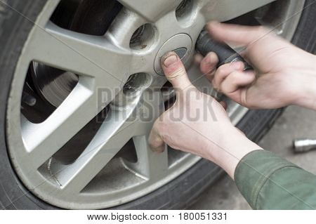 Hand of mechanic removing a car wheel nut closeup with blurred motion