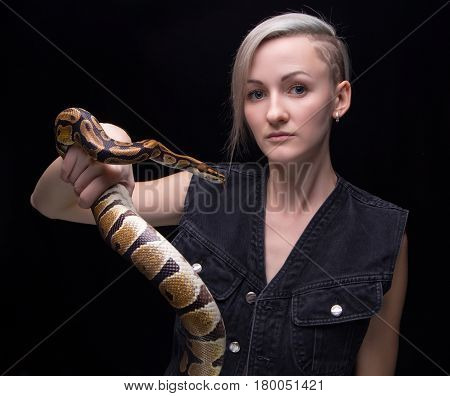 Portrait of blond woman holding python on black background