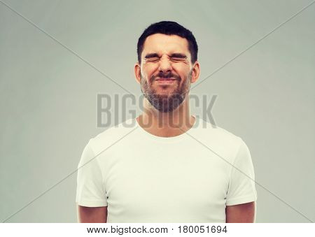 emotion and people concept - young wrying man over gray background