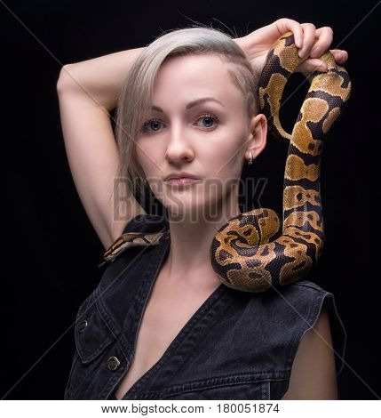 Blond woman with python on black background