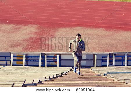 fitness, sport, exercising and lifestyle concept - man running upstairs on stadium
