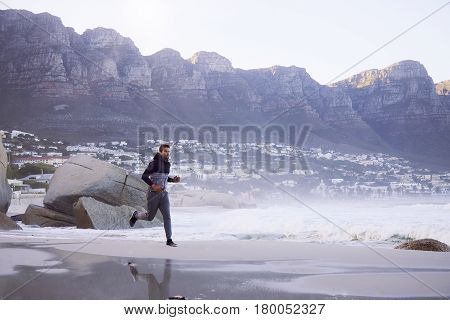 Sporty Guy jogging on beach South Africa