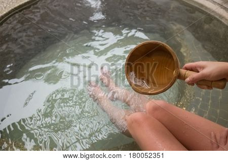 woman using wooden ladle at the hot spring pool
