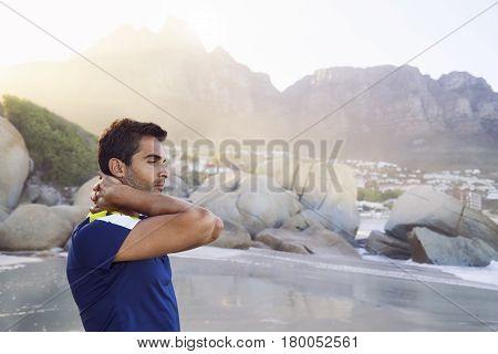 Handsome unlit dude on beach looking away