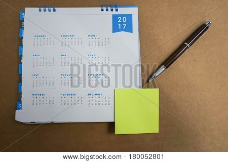 2017 calendar with mock up postit and pen for taking message in brown background