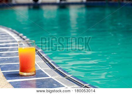 Closeup of orange juice glass standing on border of water pool