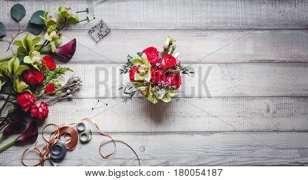 Bouquet of red roses, hearts, candle, callas, carnations and ribbons on the wooden table