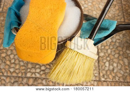 Bucket with water and soap. Sponge is in foreground and rights is broom dustpan and rag. Left on the bucket is hung rag.