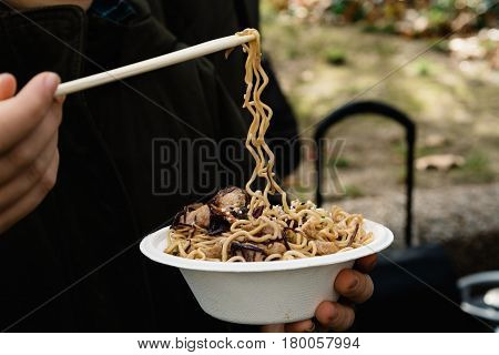 Midsection Of Woman Holding Street Food with noodles meat and vegetables. Focus on foreground