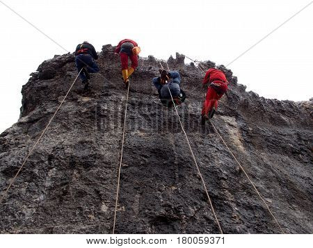 four climbers rappelling using the single rope technique