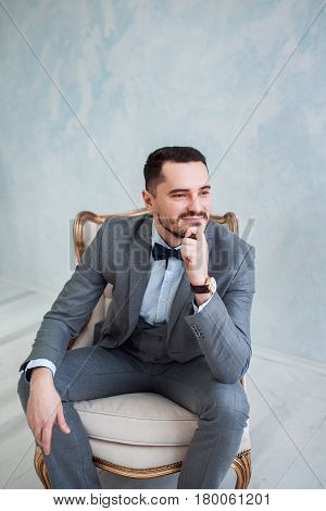 Portrait of a handsome adult man in a gray suit in the studio. The groom is waiting for the bride. Wedding