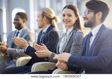 Young businesswoman looking at camera while applauding to speaker at conference