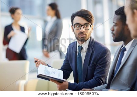 Serious businesman looking at one of colleagues during discussion