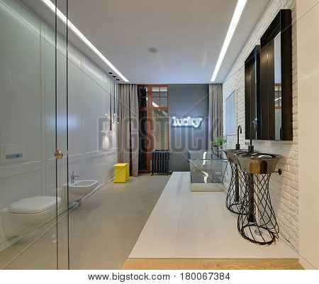 Bathroom in a loft style with light and brick walls and glass doors. There is a white toilet and a bidet, reticulated sinks with mirrors, glass bath, glowing signboard, yellow stool, vintage radiator.