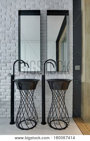 Two stylish reticulated black sinks with faucets on the background of the mirrors and light brick wall. Closeup. Vertical.