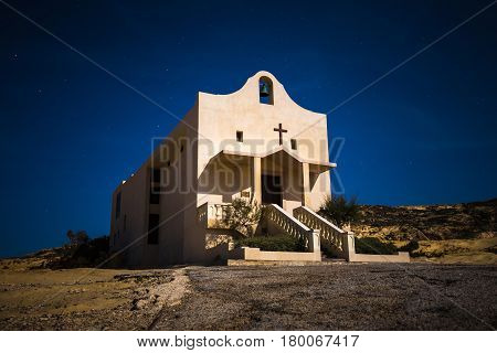 Gozo Malta - The Saint Anne or Sant' Anna Chapel at Dwejra bay by night on the island of Gozo at full moon