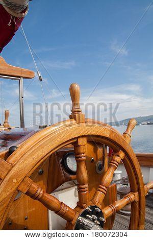 Old boat steering wheel from wood. Blue sky