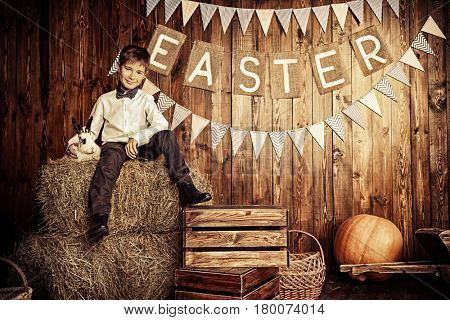 Easter holidays. Happy child boy sitting on a haystack with Easter Bunny.