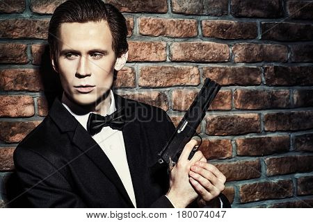 Handsome man in black suit holding a gun. Secret agent, mafia.