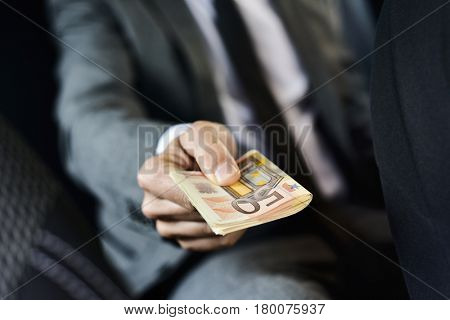 a young caucasian man in an elegant gray suit sitting in the back seat of a car offers a wad of euro bills to the front