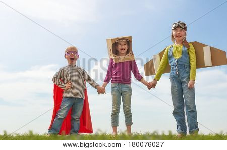 Children in astronaut, pilot and super hero costumes are laughing, playing and dreaming. Portrait of funny kids on nature. Family friends games outdoors.
