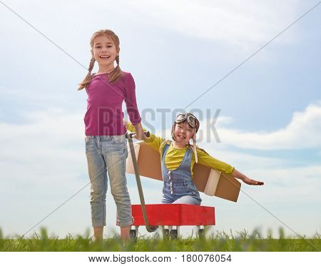 Little children play astronaut. Girls having fun in the park. Kid in an astronaut costume dreams of becoming a spaceman. Family games outdoors.