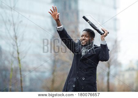 Portrait of smiling African-American businessman waving, raising his hand trying to catch taxi in winter city street, covering head with briefcase from snow