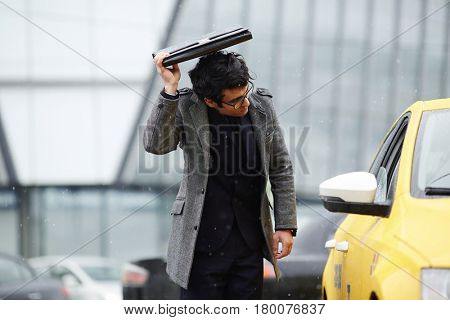 Portrait of disheveled young businessman trying to catch taxi cab in cold rainy autumn street, covering head with briefcase