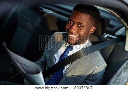 Portrait of confident African - American businessman riding in backseat of car  looking at camera out lit by sunlight, smiling cheerfully while reading newspaper