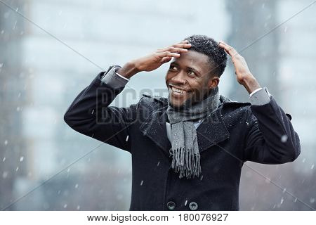 Portrait of handsome African-American businessman smiling cheerfully while brushing snow off his head in winter city street