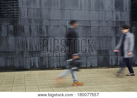 Blurred shapes of two unrecognizable  people walking fast past each other against concrete grey background