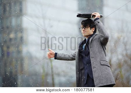 Portrait of young Middle - Eastern businessman standing in street covering head with briefcase from snow, and trying to catch taxi