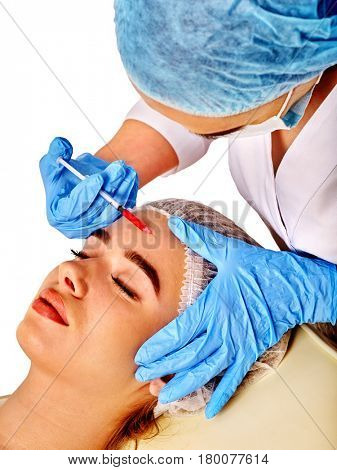 Filler injection for female forehead face. Plastic aesthetic facial surgery by doctor in beauty clinic. Beauty woman giving njections. Doctor in medical gloves with syringe.