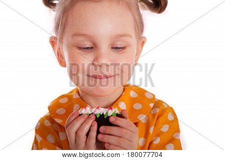 A little girl holds a cake in her hands and looks and looks forward to eating with an appetite. close-up